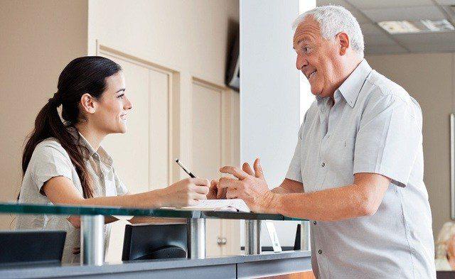 Homem conversando com secretária sorrindo