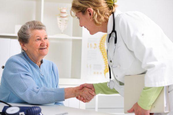 Dentista sorrindo apertando a mão de uma paciente idosa