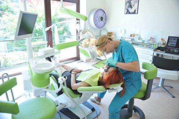 Dentista prestando atendimento em uma paciente deitada na cadeira