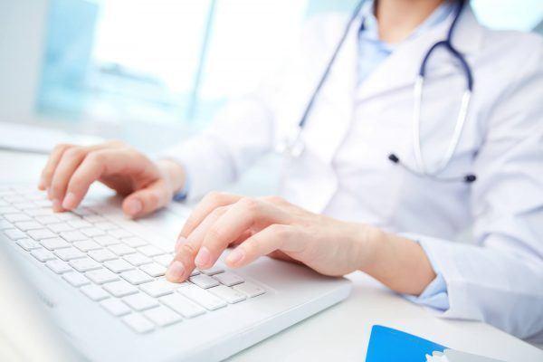 Médica digitando em seu notebook