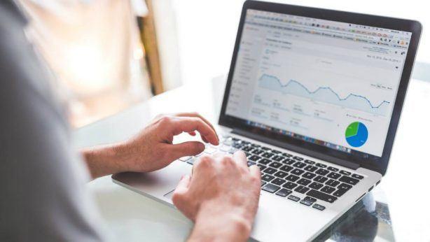 Homem usando notebook com tela mostrando gráficos