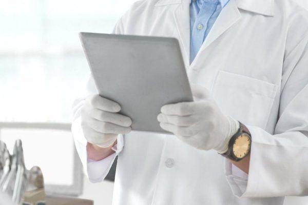 Dentista analisando sua agenda em um tablet