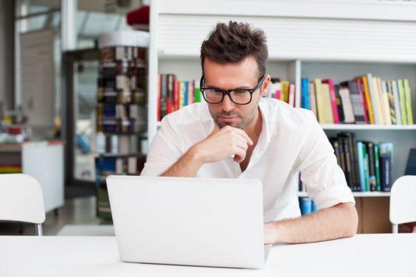 Homem lendo alguma coisa na tela de seu computador