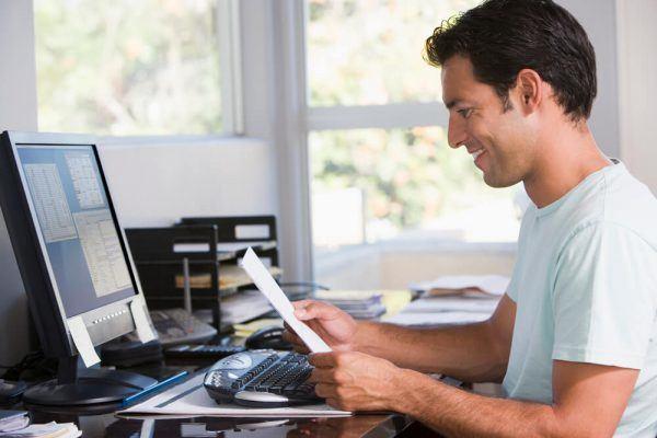 Homem olhando para papel em frente ao seu computador