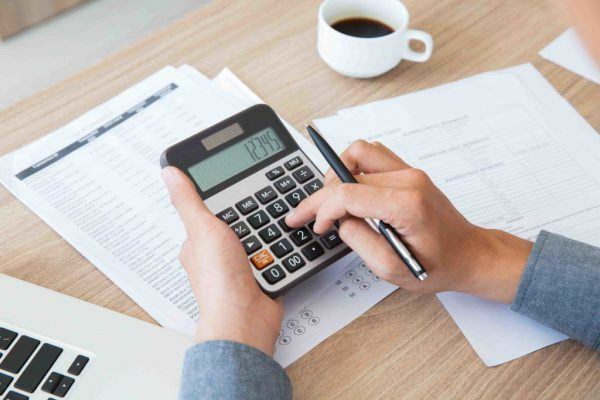 Homem mexendo na calculadora com documentos sobre a mesa