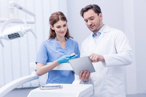 Dois dentistas conversando enquanto o homem mostra alguma coisa na prancheta para a mulher