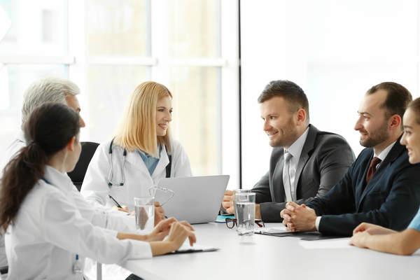 Três médicos conversando com três executivos