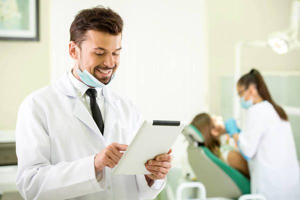 Homem sorrindo enquanto mexe em um tablet com mulher e paciente ao fundo