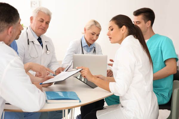 Diversos médicos conversando olhando para pranchetas e notebook