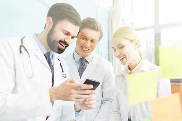 Três pessoas olhando para a tela de um celular e sorrindo ao ver o que o marketing odontológico fez por sua clínica