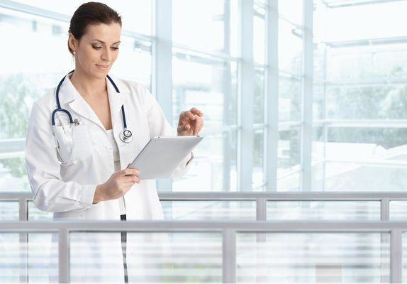 mulher médica com avental e estetoscópio mexendo em um tablet